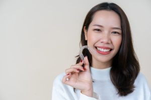 woman holding clear aligners near Marble Falls